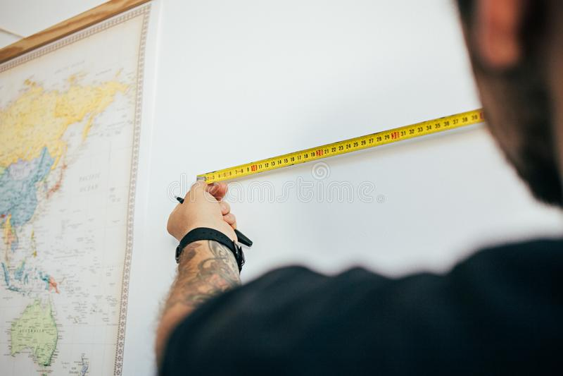 Mann misst Wand mit messendem Band stockbilder