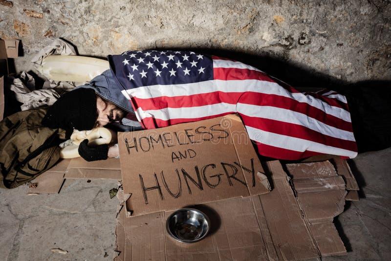 Mann mit Almosen rollen, schlafend unter amerikanischer Flagge lizenzfreie stockfotografie