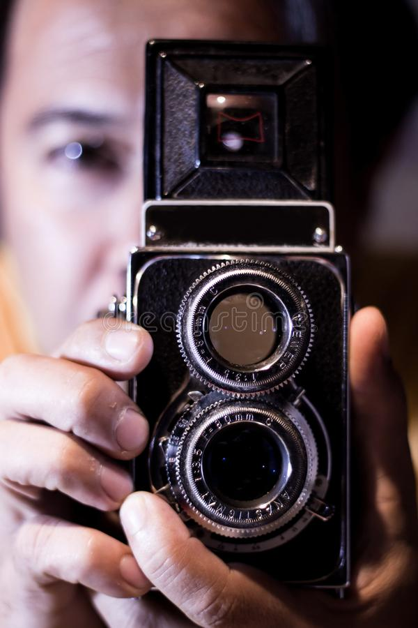 Mann mit alter Weinlesekamera in den Händen Fokus, zum von Augen zu bemannen Weinlese stilisierte Foto des Mannphotographen mit a lizenzfreies stockbild