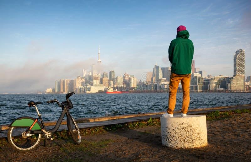 Mann mit aufpassendem Sonnenuntergang des Fahrrades über im Stadtzentrum gelegenem Panorama der Ontariosee Ufergegend und Toronto stockfotografie