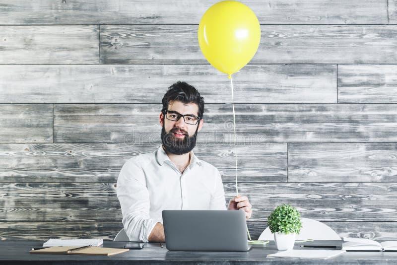 Mann mit Ballon unter Verwendung des Laptops lizenzfreie stockfotografie