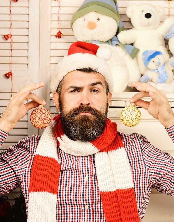 Mann mit Bart hält goldene Weihnachtsbälle als Ohrringe stockbild