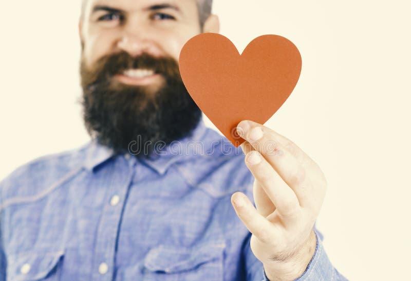 Mann mit Bart hält rotes Papierherz in der Hand, defocused stockbild