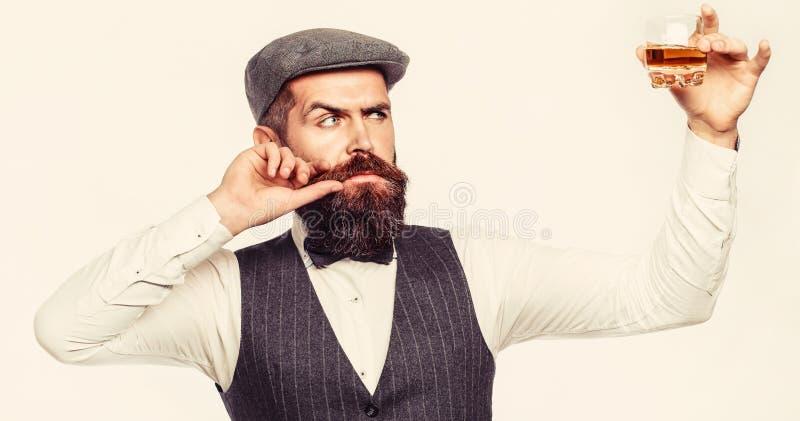 Mann mit Bart h?lt Glasweinbrand B?rtiger Getr?nkkognak Sommeliergeschmackgetr?nk Mann, der ein Glas Whisky h?lt sipping lizenzfreie stockfotos