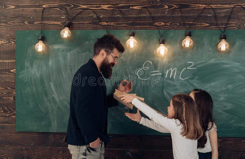 Mann mit Bart im Gesellschaftsanzug bringt Schulmädchen Physik bei Lehrer- und Mädchenschüler im Klassenzimmer nahe Tafel stockbild
