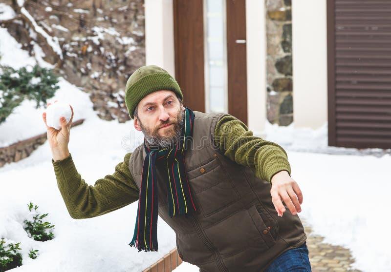 Mann mit Bart in seiner Kappe wirft Schneebälle im Yard stockbild