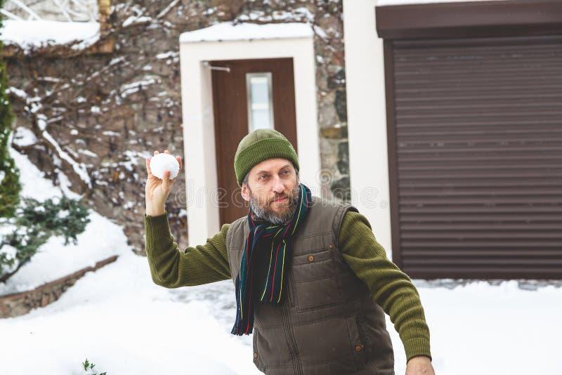 Mann mit Bart in seiner Kappe wirft Schneebälle im Yard stockfotos