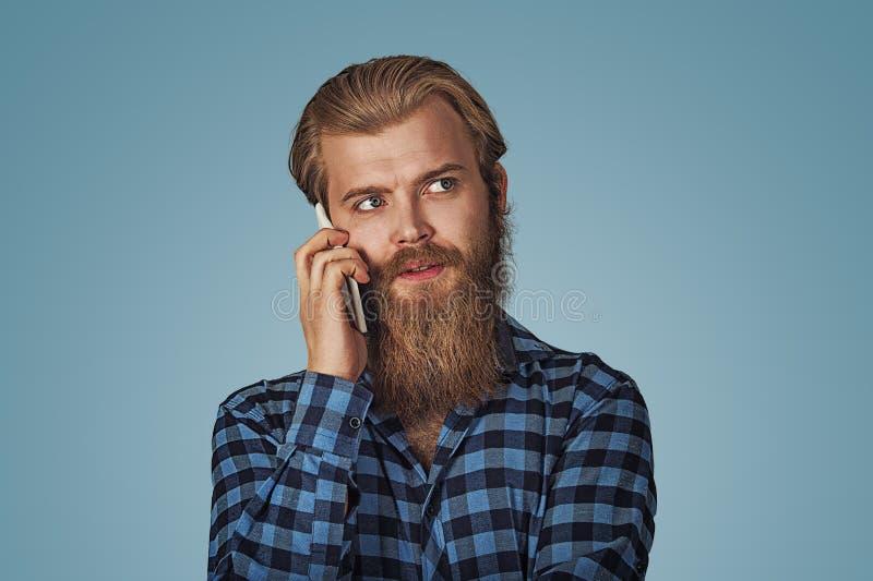 Mann mit Bart sprechend am Telefon und oben schauend, um mit Seiten zu versehen lizenzfreie stockfotografie