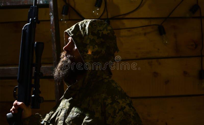 Mann mit Bart trägt mit Kapuze Kleidung der Tarnung, hölzernen Innenhintergrund Jägerkonzept Jäger, Hippie mit Gewehr stockbild