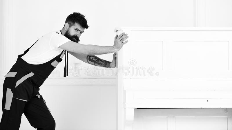 Mann mit Bart und Schnurrbart, Arbeitskraft im Overall drückt Klavier, weißen Hintergrund Kurier liefert Möbel im Falle lizenzfreie stockfotos