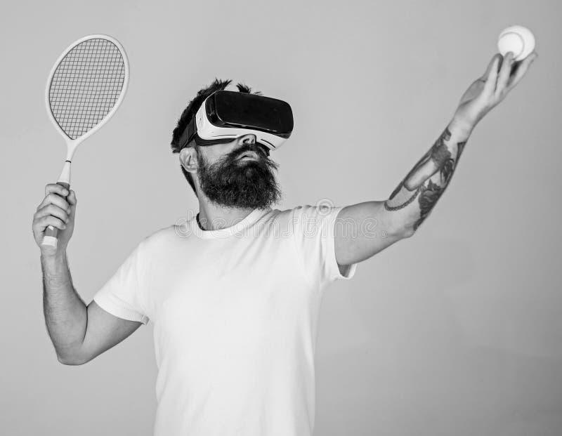 Mann mit Bart in VR-Gläsern, grauer Hintergrund Hippie auf starker moderner Technologie des Gesichtsgebrauches für Sportspiele stockfotos