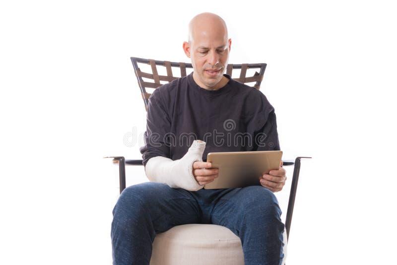 Mann mit dem Arm warf unter Verwendung einer zugänglichen Tablette lizenzfreie stockbilder