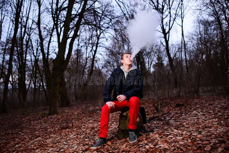 Mann mit dem Bart, der das elektronische sigarette im Freien raucht lizenzfreie stockbilder