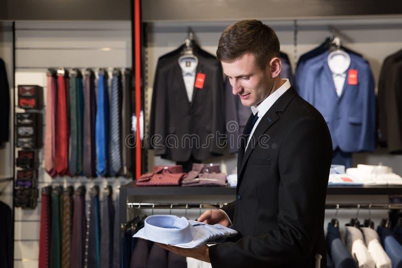 Mann mit dem Bart, der Hemd in einem Shop wählt lizenzfreies stockfoto