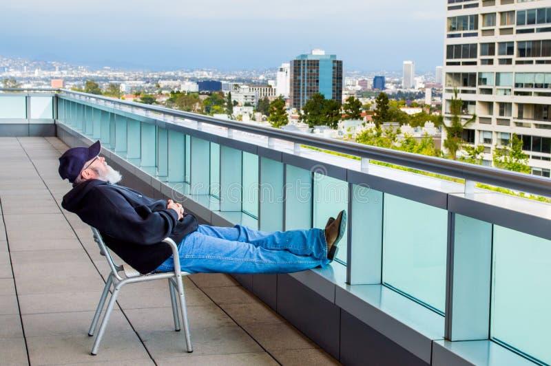 Mann mit dem Bart, der im Stuhl auf Balkon sitzt lizenzfreie stockfotos