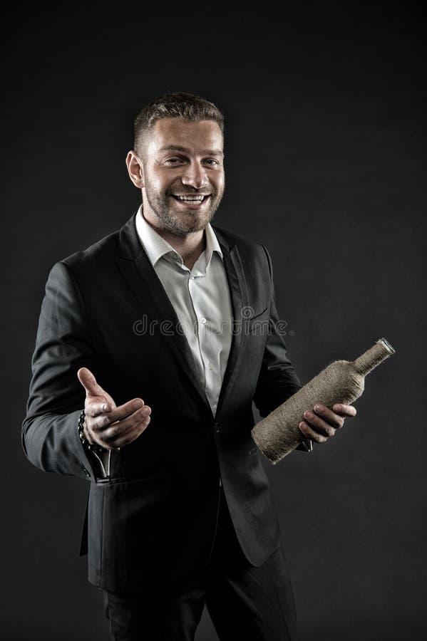 Mann mit dem Borstenblick nett und gastfreundlich Gastfreundschaftskonzept Mann auf dem glücklichen Gesicht, das mit Flasche von  stockbild