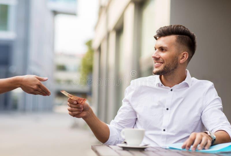 Mann mit dem Eurogeld, das für Kaffee am Café zahlt lizenzfreies stockfoto