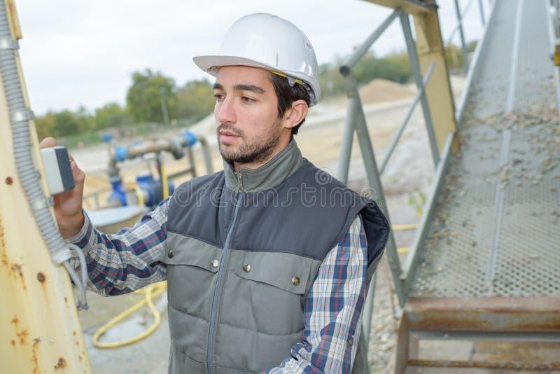 Mann mit dem Finger auf Schalter im Steinbruch stockbilder