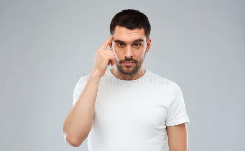 Mann mit dem Finger am Tempel über grauem Hintergrund stockfoto
