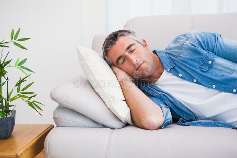 Mann mit dem grauen Haar schlafend auf der Couch lizenzfreies stockbild
