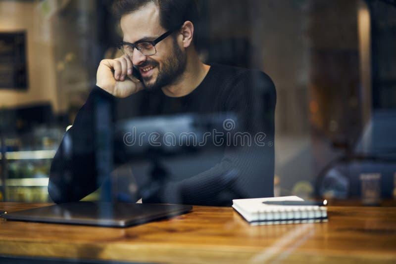 Mann mit dem Handy, der auf der Reise vorbereitet Artikel und Multimedia ist, archiviert, um mit Nachfolgern zu teilen stockbild
