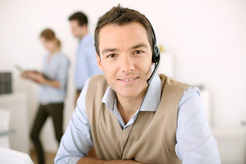 Mann mit dem Haupttelefon, das Kundendienst bereitstellt stockbild