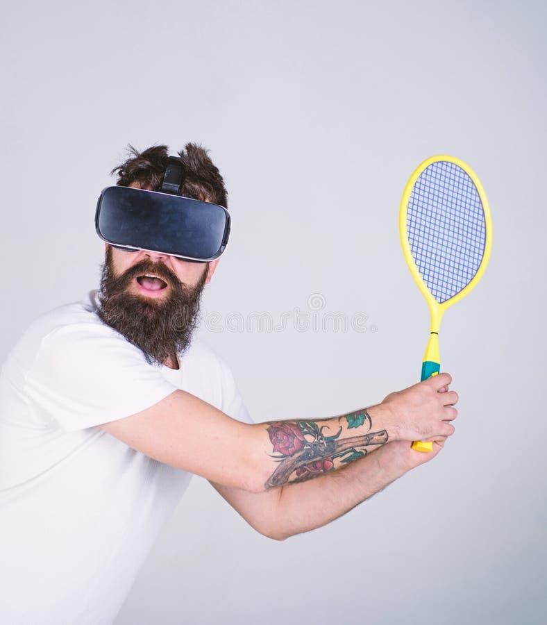 Mann mit dem Hippie-Bart, der Tennis in der virtuellen Realität, Sportkonzept spielt Bärtiger Mann in VR-Schutzbrillen, die Sport lizenzfreies stockbild