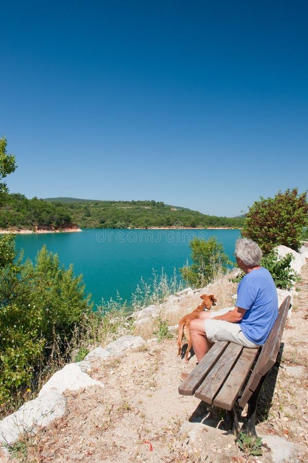 Mann mit dem Hund, der in der französischen Landschaft sitzt lizenzfreies stockfoto