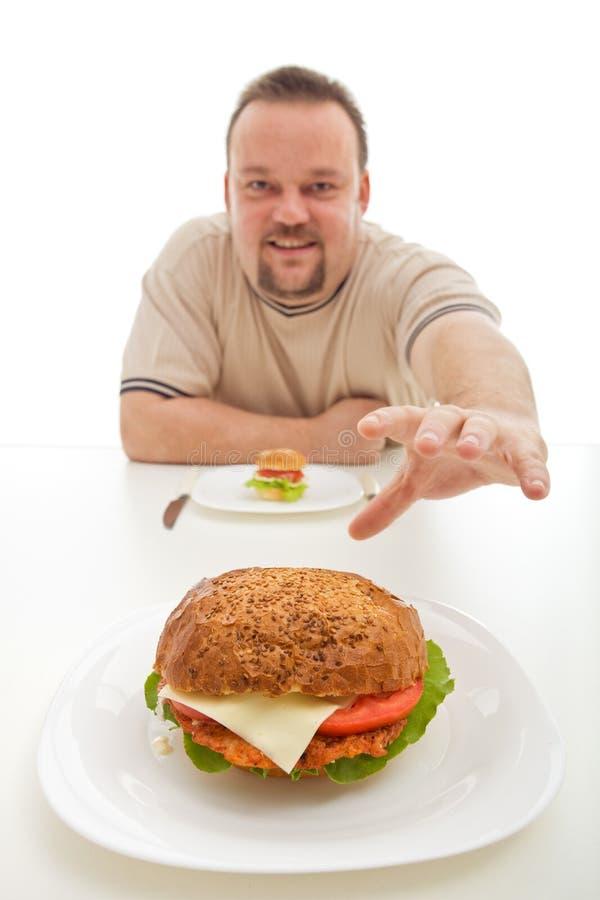 Mann mit dem kleinen Hamburger, der für ein größeres erreicht stockbild