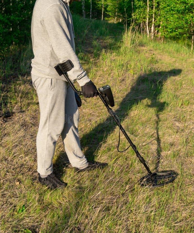 Mann mit dem Metalldetektor, der nach einem Schatz sucht lizenzfreies stockfoto