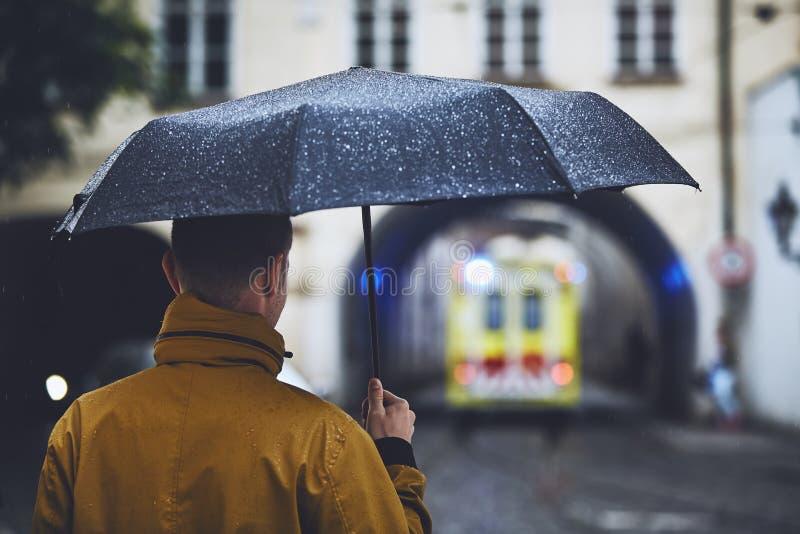 Mann mit dem Regenschirm, der betrachtet, lassend Krankenwagenauto lizenzfreie stockfotos