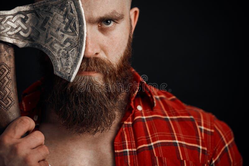 Mann mit dem Schnurrbart hält eine Kampfaxtabdeckung sein Auge und schaut auf Kamera auf schwarzem Hintergrund lizenzfreie stockfotos