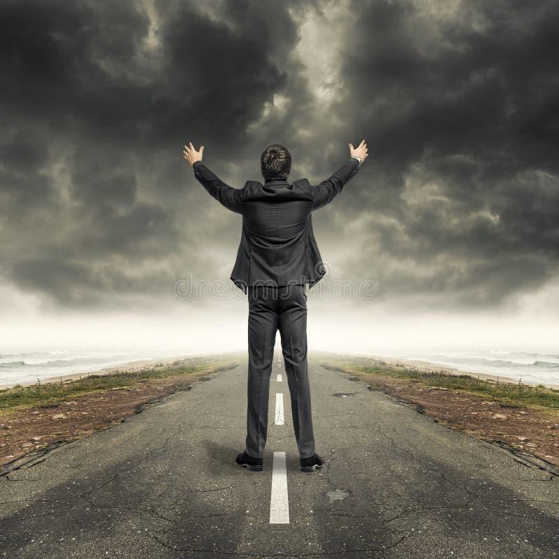 Mann mit den angehobenen Händen auf Asphaltlandschaftsstraße stockfotografie
