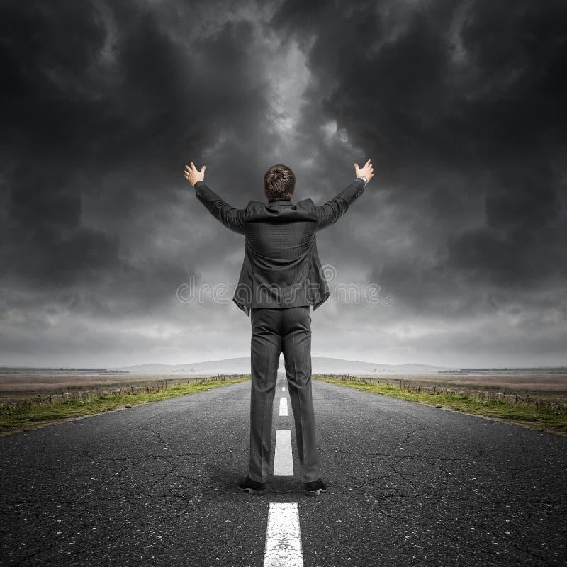 Mann mit den angehobenen Händen auf Asphaltlandschaftsstraße stockfotos