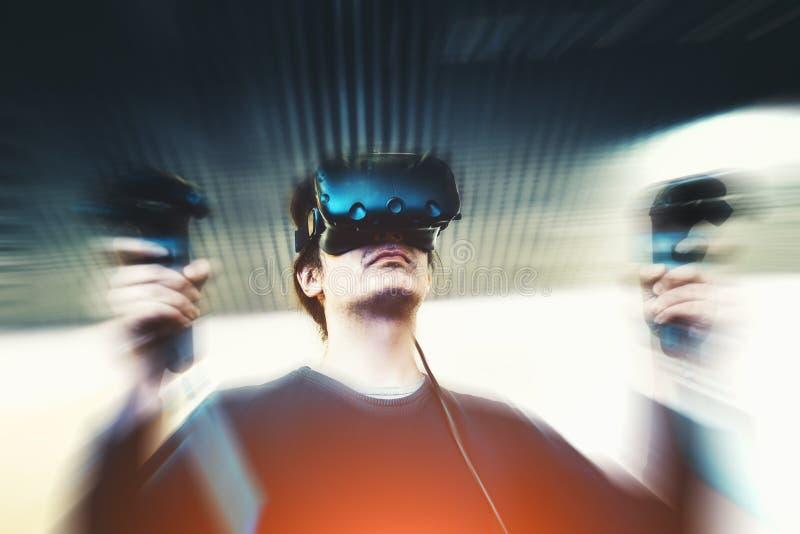 Mann mit den Gläsern der virtuellen Realität, die Videospiel, Bewegungsunschärfeeffekt spielen stockfoto