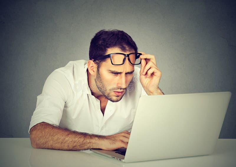 Mann mit den Gläsern, welche die Sehvermögenprobleme verwechselt mit Laptop haben lizenzfreie stockbilder