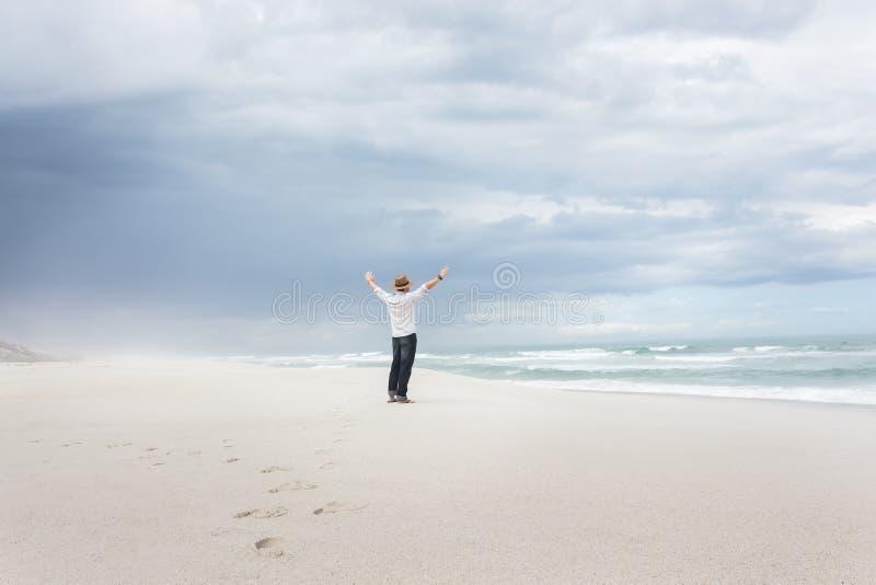 Mann mit den Händen in der Luft Freiheit auf Strand feiernd stockbild
