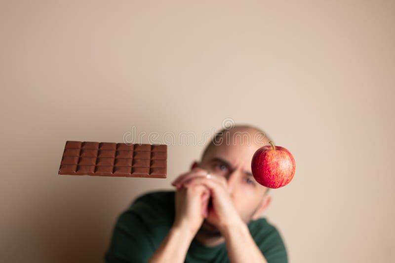 Mann mit den Händen schloss das Betrachten eines Apfels, der nahe bei einem Schokoriegel frei schwebt lizenzfreie stockfotos