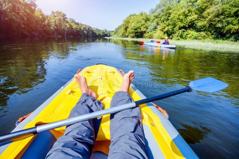 Mann mit den Kindern, die auf dem Fluss an einem sonnigen Tag während der Sommerferien Kayak fahren stockbild