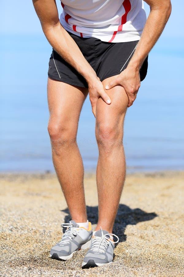 Mann mit den Verstauchungsschenkelmuskeln Mannläuferverstauchungs-Schenkelmuskeln lizenzfreie stockfotos