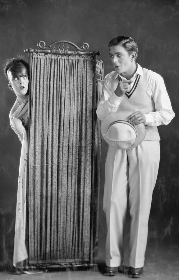 Mann mit der Frau, die hinter Schirm ändert (alle dargestellten Personen sind nicht längeres lebendes und kein Zustand existiert  lizenzfreie stockbilder