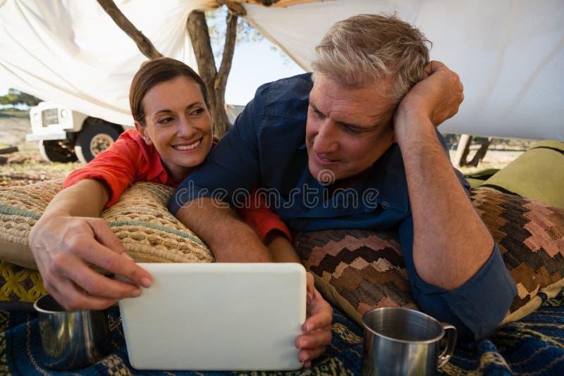 Mann mit der Frau, die Tablette im Zelt betrachtet stockbilder