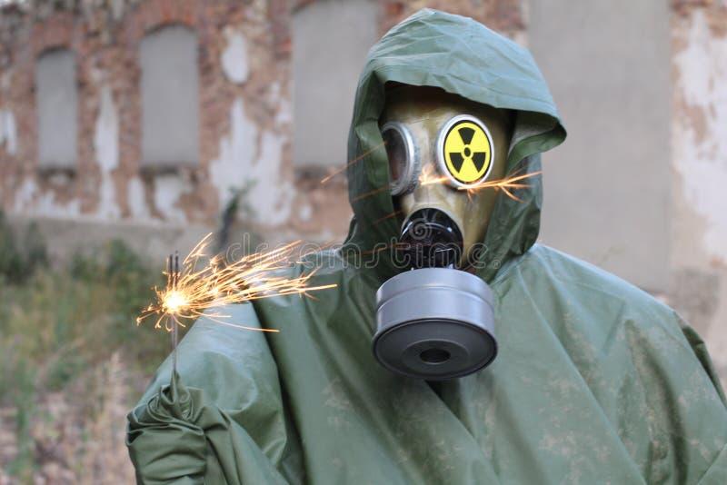Mann mit der Gasmaske, die eine Wunderkerze hält stockbilder