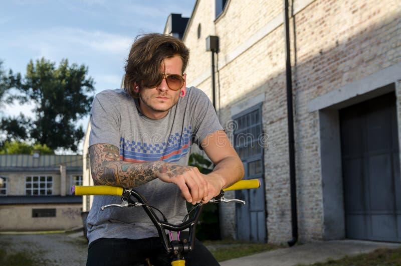 Mann mit der Haltung, die auf extremem Fahrrad sitzt stockfotografie