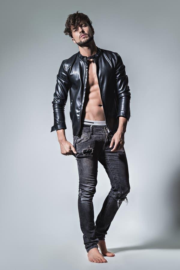 Mann mit der Haltung, die in der Lederjacke und in den Jeans aufwirft lizenzfreies stockbild