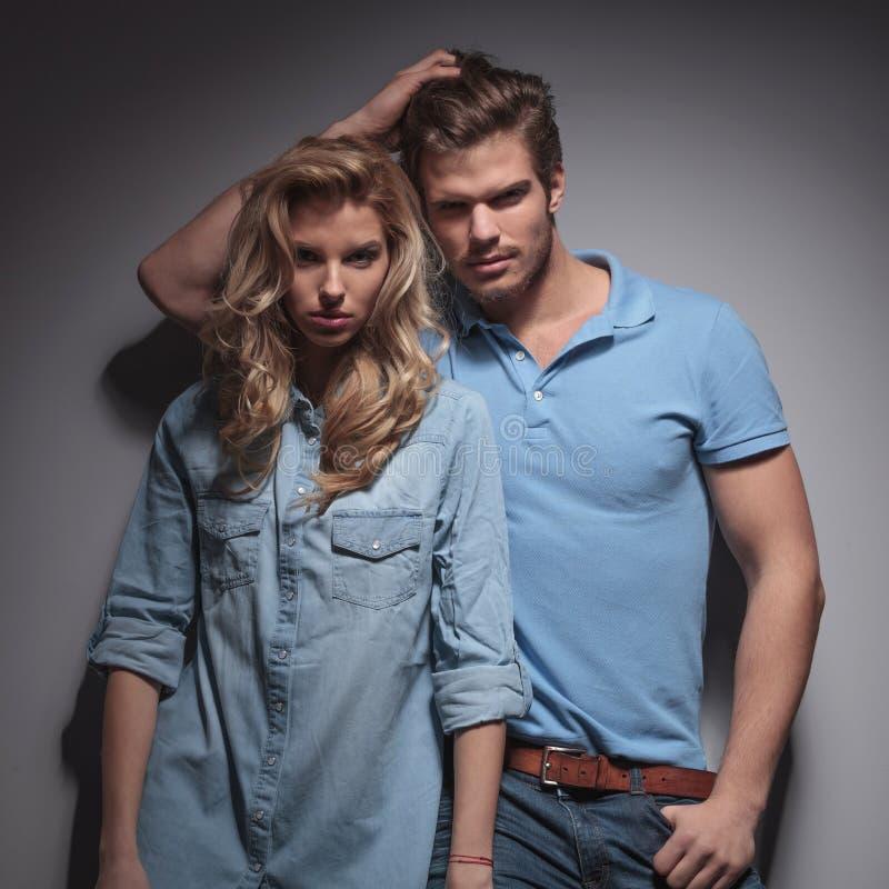 Mann mit der Hand in seinem Haar, das an der Freundin sich lehnt lizenzfreie stockfotos