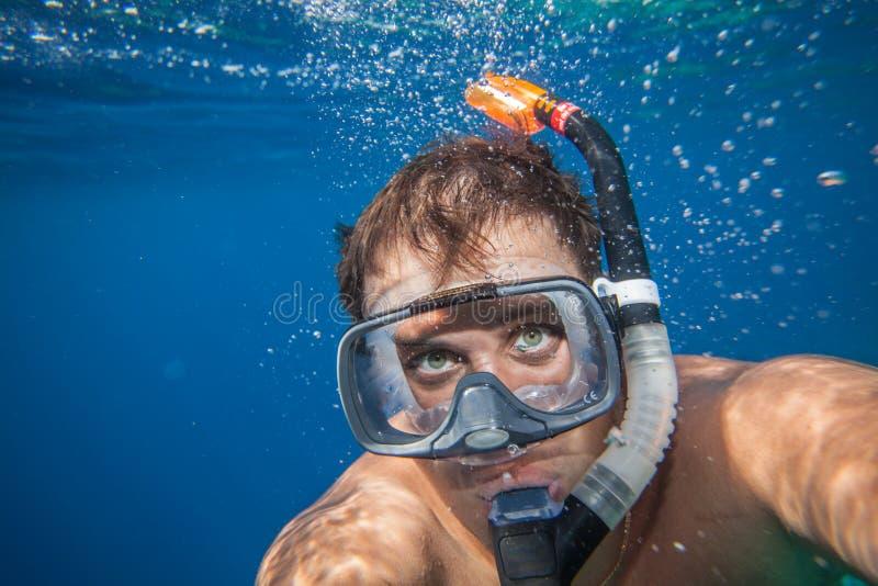 Mann mit der Maske, die im klaren Wasser schnorchelt lizenzfreies stockbild