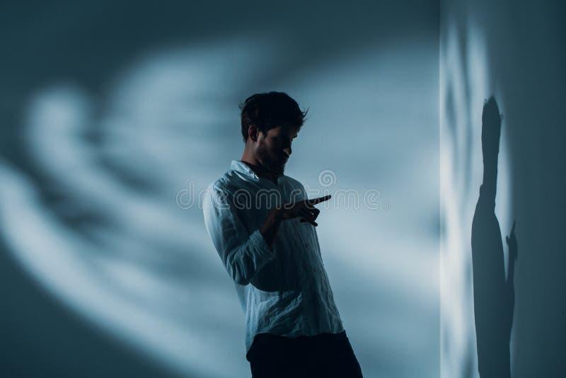 Mann mit der Schizophrenie, die allein in einem Raum zeigend auf seinen Schatten auf der Wand, wirkliches Foto steht lizenzfreie stockbilder