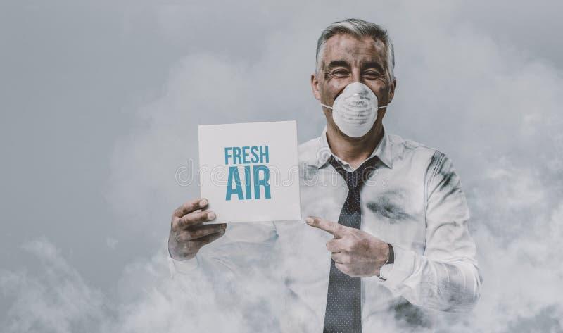Mann mit der Verschmutzungsmaske, die ein Zeichen hält lizenzfreies stockbild