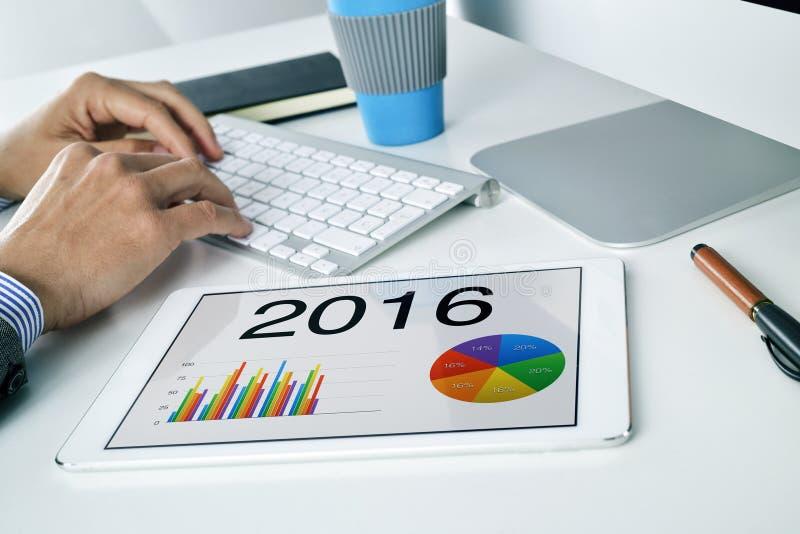 Mann mit der wirtschaftlichen Prognose für 2016 in seiner Tablette lizenzfreie stockfotografie